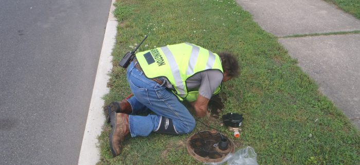Public Works Staff Installing Water Meter in a Yard with the Meter Pit Open